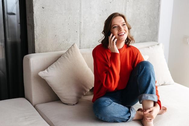 Wesoła młoda niedbale ubrana kobieta siedzi na kanapie w domu, rozmawiając przez telefon komórkowy