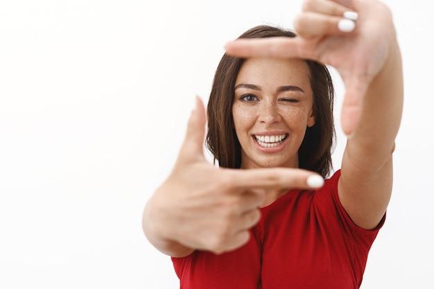 Wesoła młoda, optymistyczna kobieta czuje się szczęśliwym, szukając idealnego kąta, robiąc oprawki palców i patrząc żartobliwie mrugając, uśmiechając się radośnie