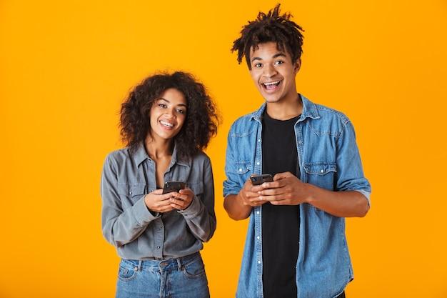 Wesoła młoda para afrykańskich stojących na białym tle, przy użyciu telefonów komórkowych