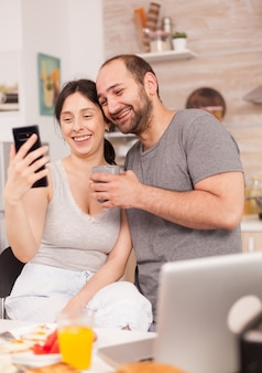 Wesoła młoda para biorąc selfie podczas pysznego śniadania w kuchni. radosny żonaty mąż i żona robiąc śmieszne miny podczas robienia zdjęć podczas śniadania w kuchni.