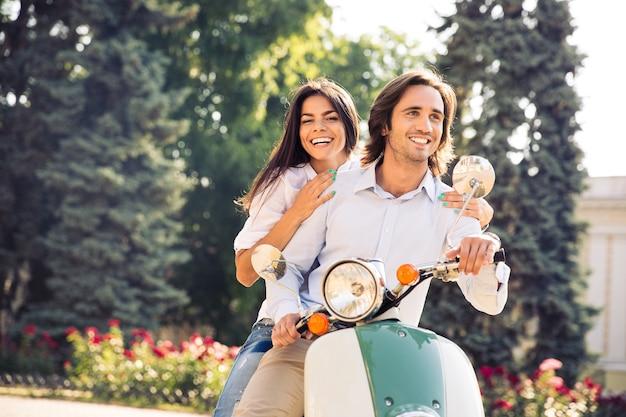 Wesoła młoda para jedzie na skuterze w mieście z zabawą