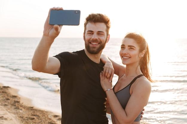 Wesoła młoda para kochających zrobić selfie przez telefon komórkowy.