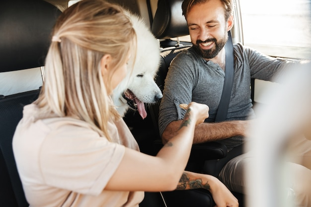 Wesoła młoda para na wycieczce samochodowej z psem