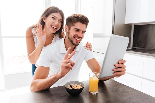 Wesoła młoda para prowadzi czat wideo online z tabletem w kuchni