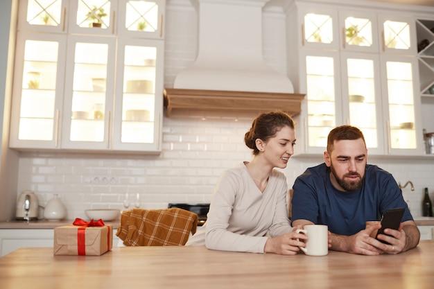 Wesoła młoda para rasy kaukaskiej siedzi przy stole w kuchni i pije kawę podczas surfowania po sieci...