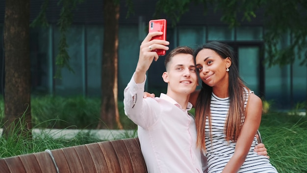 Wesoła młoda para robi selfie siedząc na ławce na świeżym powietrzu, spędzając czas w dużym parku