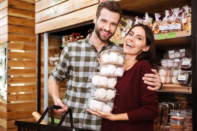 Wesoła młoda para robi zakupy i kupuje pianki w sklepie spożywczym