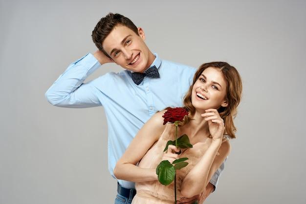 Wesoła młoda para romans obejmuje związek czerwona róża światło stylu życia