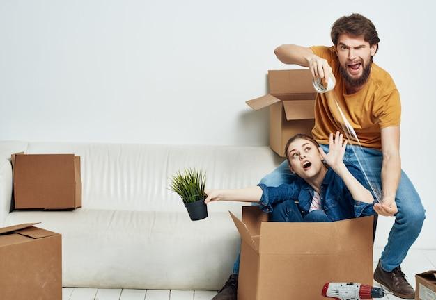 Wesoła młoda para rozpakowywania pudeł przenosi się do nowego stylu życia w mieszkaniu. zdjęcie wysokiej jakości