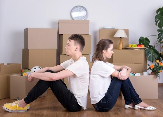 Wesoła młoda para siedzi na podłodze.