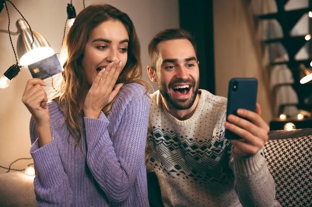 Wesoła młoda para siedzi razem na kanapie w domu, trzymając telefon komórkowy, pokazując plastikową kartę kredytową