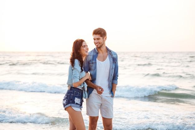 Wesoła młoda para śmiejąca się i spacerująca po plaży