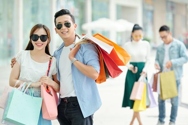 Wesoła młoda para stoi na zewnątrz okulary przeciwsłoneczne z torby na zakupy
