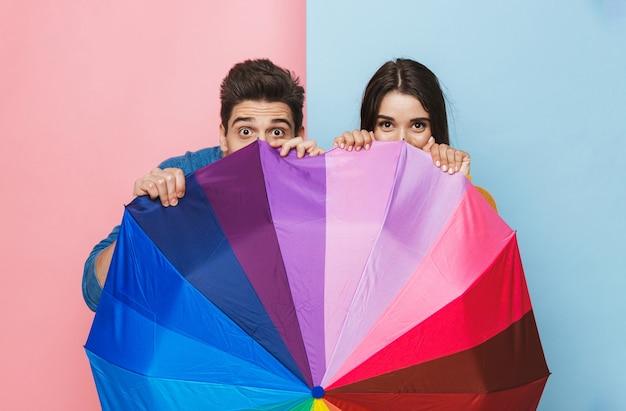 Wesoła młoda para stoi z parasolem