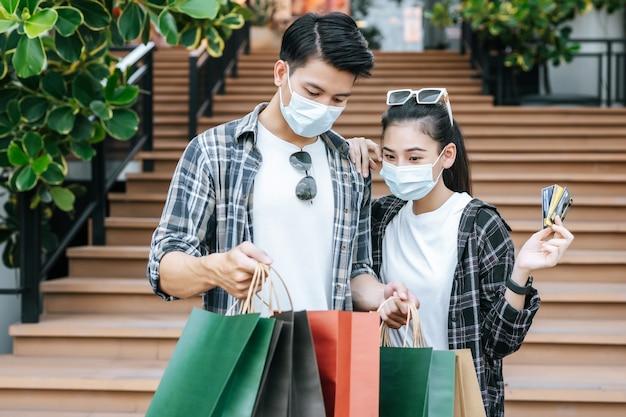 Wesoła młoda para trzymająca kilka papierowych toreb na zakupy