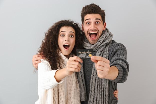 Wesoła młoda para ubrana w swetry i szaliki stojąc na białym tle nad szarą ścianą, pokazując plastikową kartę kredytową