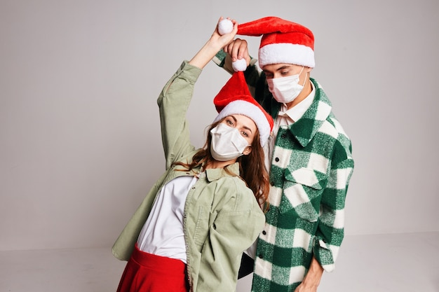 Wesoła młoda para ubrana w ubrania noworoczne maska medyczna kwarantanny