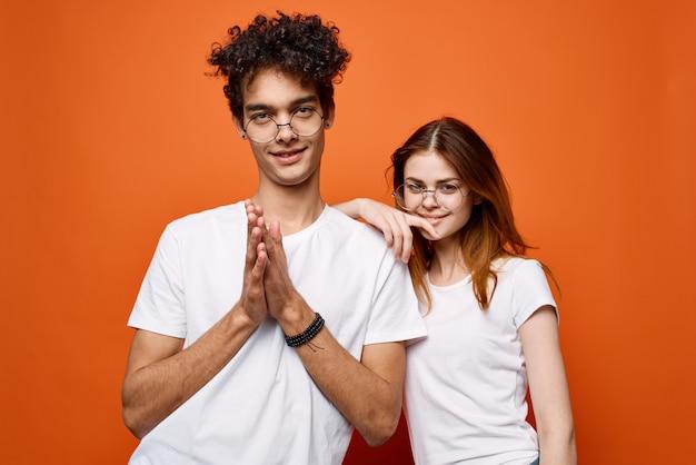 Wesoła młoda para w białych koszulkach pozowanie na pomarańczowym tle