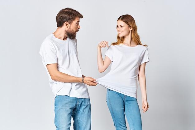 Wesoła młoda para w białych koszulkach projektuje moda zabawa kopia przestrzeń