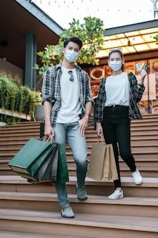 Wesoła młoda para w masce trzymająca papierową torbę na zakupy