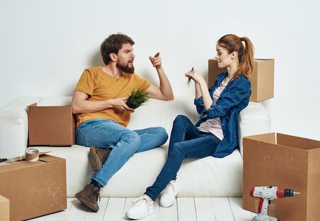 Wesoła młoda para w polach mieszkania z rzeczami w ruchu