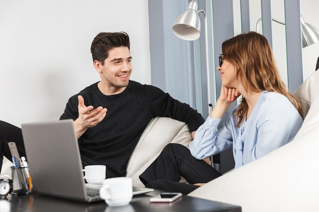 Wesoła młoda para współpracowników pracujących razem w biurze, koncepcja współpracy zespołowej, za pomocą laptopa