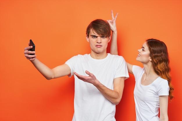Wesoła młoda para z telefonami w rękach technologia mody