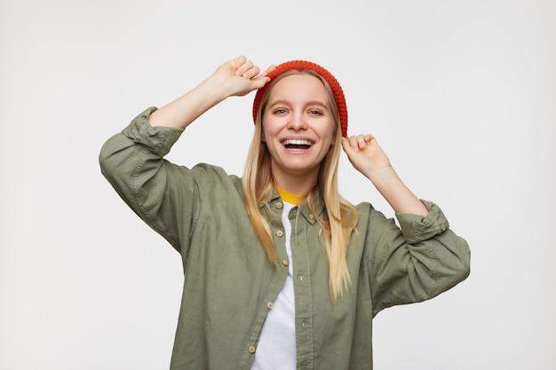 Wesoła młoda piękna białogłowa kobieta z naturalnym makijażem wyglądająca szczęśliwie z szerokim uśmiechem i trzymająca uniesione ręce na głowie, odizolowana na niebiesko