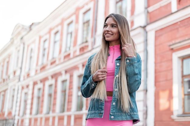 Wesoła młoda piękna blond kobieta z uroczym uśmiechem w modnej niebieskiej dżinsowej kurtce w efektownym różowym letnim garniturze spaceruje po mieście w pobliżu zabytkowego budynku.