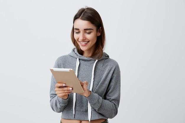 Wesoła młoda piękna brunetka kaukaski studentka o długich ciemnych włosach w swobodnej szarej bluzie z kapturem uśmiechnięty, trzymając w rękach cyfrową tabletkę, przeglądając śmieszne zdjęcia przyjaciół