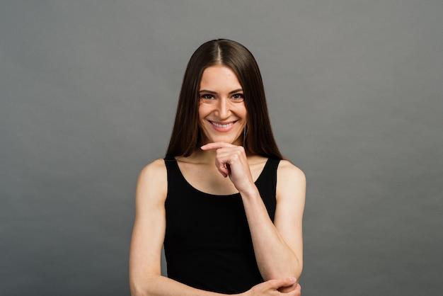 Wesoła młoda piękna dziewczyna uśmiecha się, mrugając, pokazując język, patrząc na kamery na szarym tle. emocjonalny.