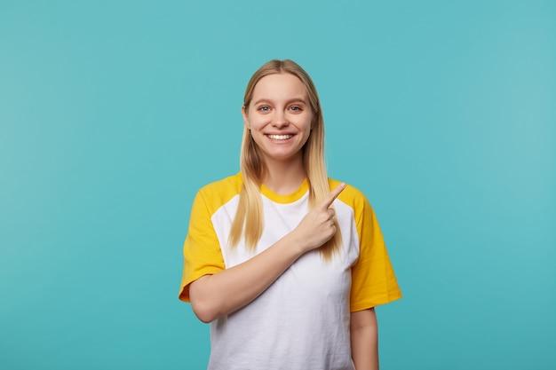 Wesoła młoda piękna jasnowłosa kobieta z przypadkową fryzurą pokazującą na bok z palcem wskazującym i szeroko uśmiechającą się do kamery, stojącą na niebieskim tle
