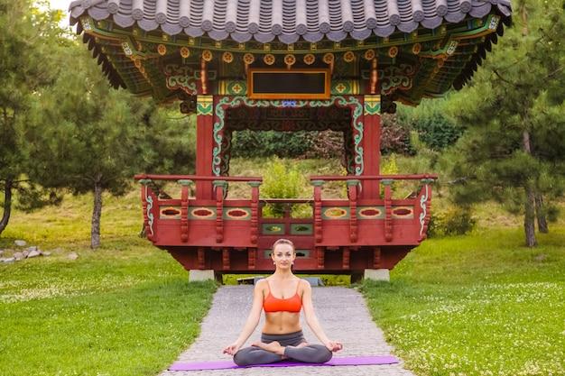 Wesoła młoda piękna kobieta praktykuje i pozowanie jogi w parku azji wschodniej. baddha konasana poza.