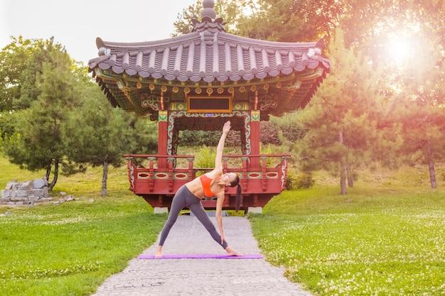 Wesoła młoda piękna kobieta praktykuje i pozowanie jogi w parku azji wschodniej. poza trójkąt.