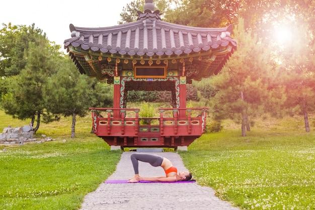 Wesoła młoda piękna kobieta praktykuje i pozowanie jogi w parku azji wschodniej.