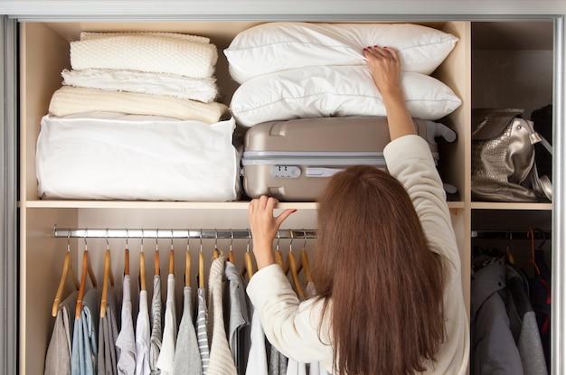 Wesoła młoda piękna kobieta wyciąga poduszki z górnej półki. . skopiuj miejsce. ubrania do przechowywania.
