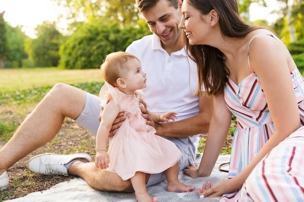 Wesoła młoda rodzina z małą córeczką spędzającą razem czas