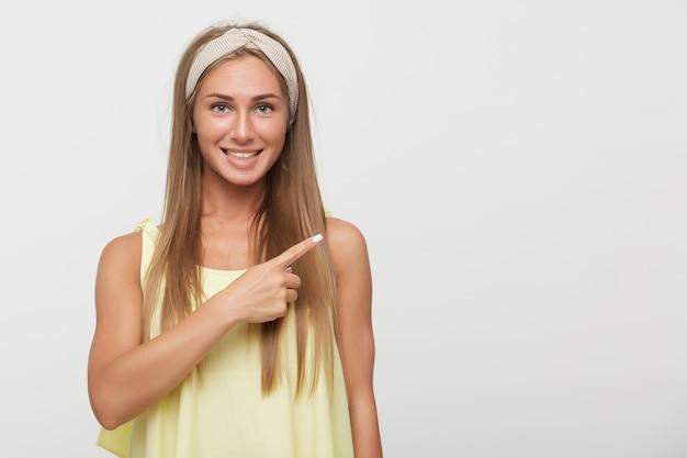Wesoła młoda śliczna blondynka z naturalnym makijażem, uśmiechnięta szeroko, pokazująca na bok palcem wskazującym, ubrana w ubranie, stojąc na białym tle