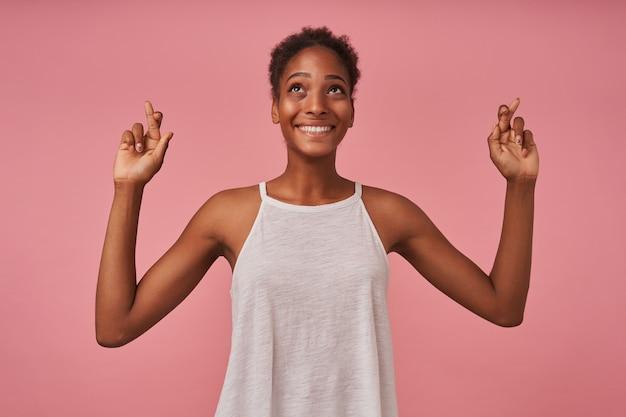 Wesoła młoda śliczna brązowowłosa kręcona suczka z szerokim uśmiechem, patrząc w górę i trzymającą kciuki, odizolowana na różowej ścianie