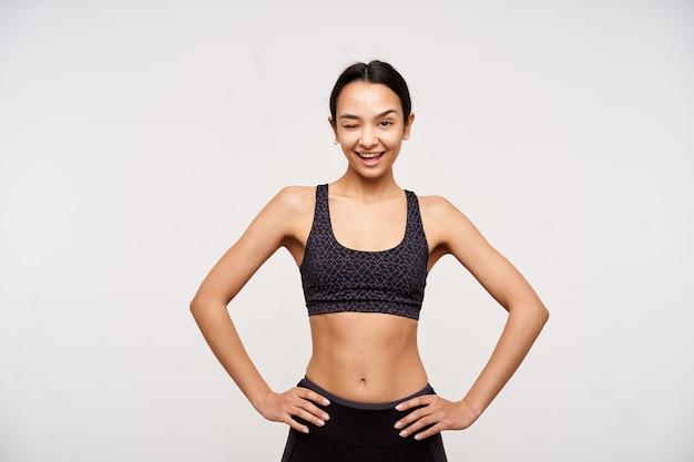 Wesoła młoda śliczna ciemnowłosa sportowa kobieta trzyma ręce na talii, jednocześnie radośnie mrugając z przodu, stojąc nad białą ścianą w czarnym topie i leginsach