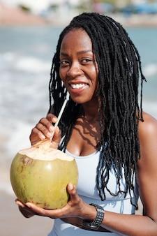 Wesoła młoda sportsmenka z dredami stoi na plaży i trzyma kokos ze słomą w środku i patrzy na kamerę