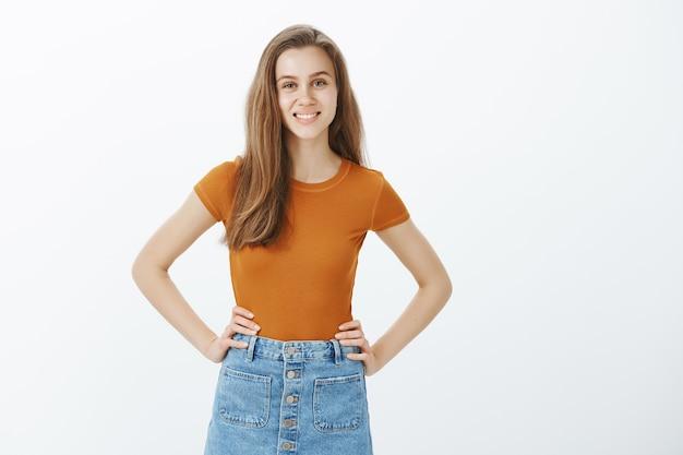 Wesoła młoda studentka patrząc optymistycznie, uśmiechając się i trzymając się za ręce w talii