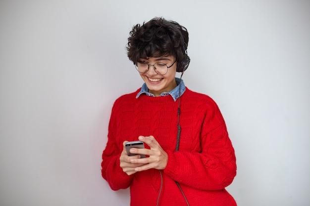 Wesoła młoda stylowa piękna krótkowłosa kręcona kobieta w słuchawkach i trzymająca smartfona w uniesionych rękach, szeroko uśmiechnięta, patrząc na ekran, odizolowana na białym tle