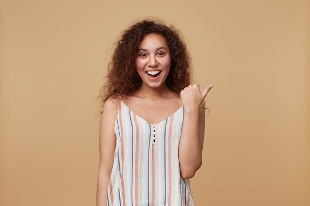 Wesoła, młoda, urocza, długowłosa, kręcona brunetka kobieta trzyma rękę uniesioną do góry, wskazując na bok z szerokim uśmiechem, pozując na beżu