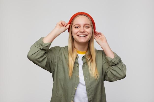 Wesoła młoda urocza długowłosa siwowłosa kobieta trzyma podniesione ręce na swoim czerwonym kapeluszu, patrząc radośnie z szerokim uśmiechem, odizolowana na niebiesko