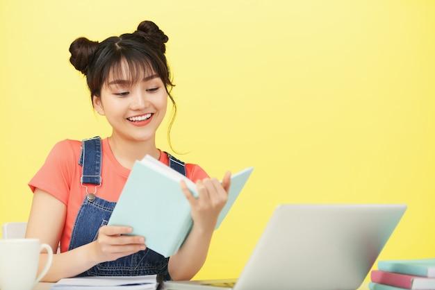 Wesoła młoda wietnamka czytająca ciekawą książkę, przygotowując się do zajęć online