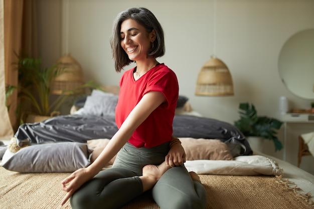 Wesoła młoda wysportowana kobieta siedzi boso na dywanie, trzymając nogi skrzyżowane, wykonując skręt kręgosłupa w pozycji siedzącej podczas zajęć jogi, wykonując ćwiczenia rozciągające, biorąc głęboki oddech, zamykając oczy