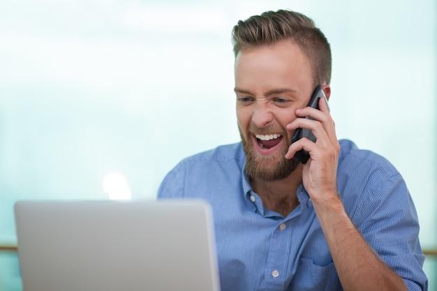 Wesoła młody człowiek rozmawia przez telefon z laptopem