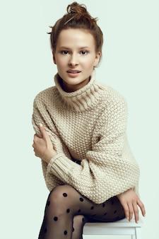 Wesoła moda hipster dziewczyna w przytulny sweter i czarne rajstopy