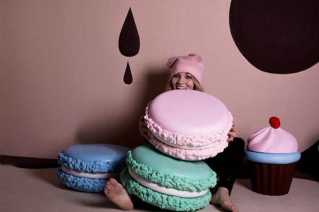 Wesoła modelka blondynka w różowej czapce bawi się z dużą babeczką i makaronikami. koncepcja wakacji